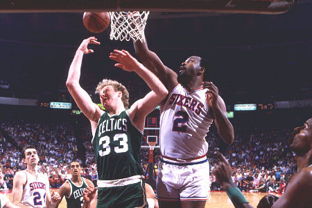 Moses Malone tapona a Larry Bird. También aparecen Robert Parish, Dennis Johnson, Bobby Jones y Danny Ainge
